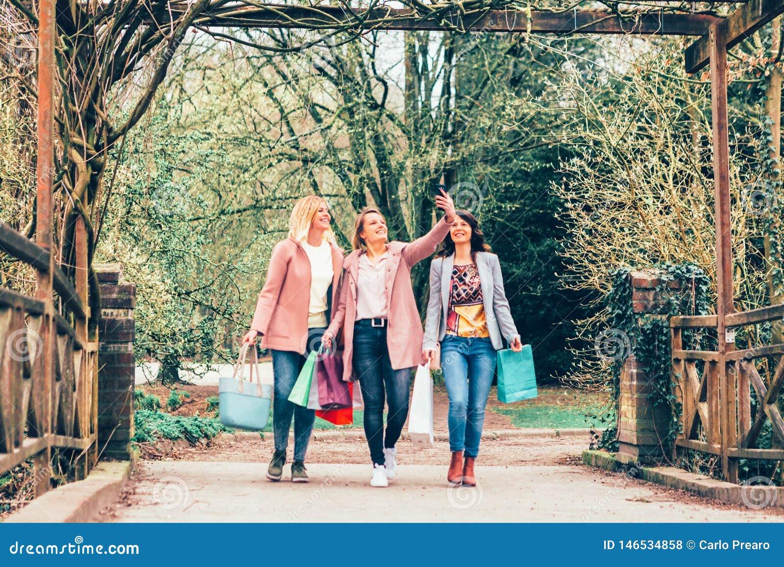 Drie jonge vrouwen in een park die een selfie met een smartphone nemen