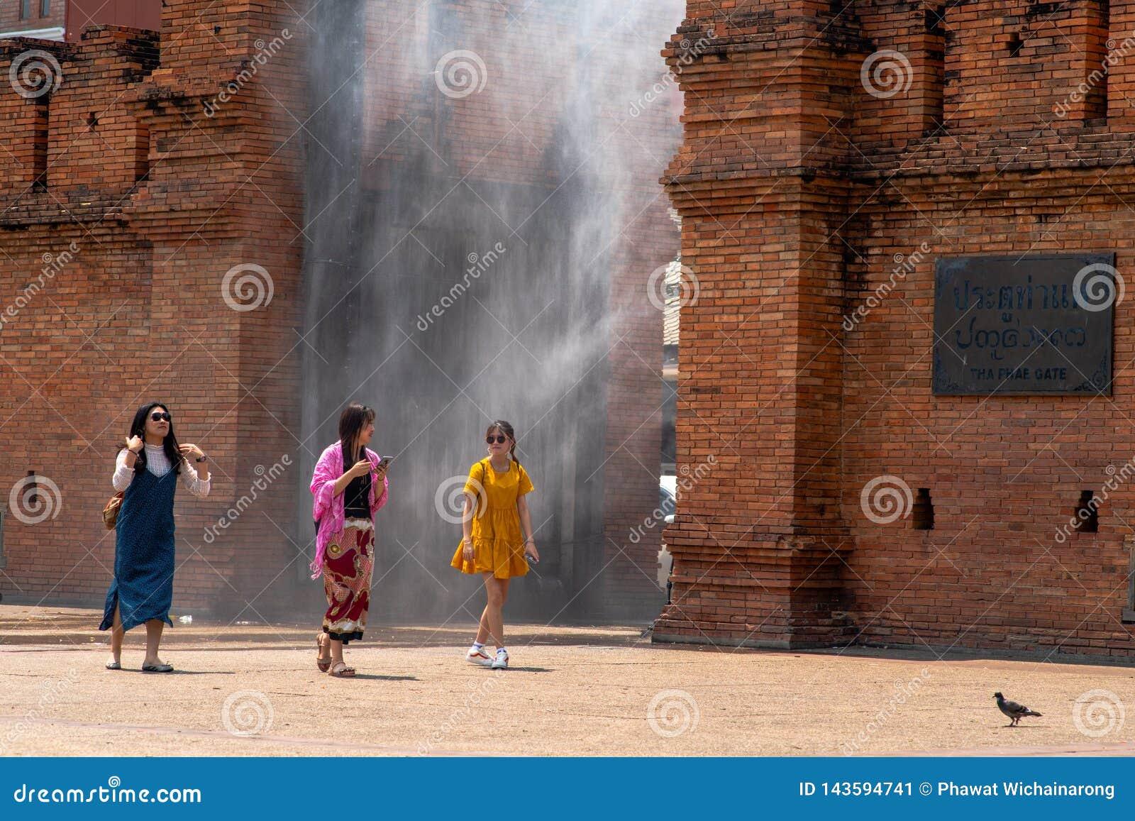 Drie jonge vrouwen met kleurrijke kleren lopen door de waternevel die bij Thapae-Poort wordt geïnstalleerd