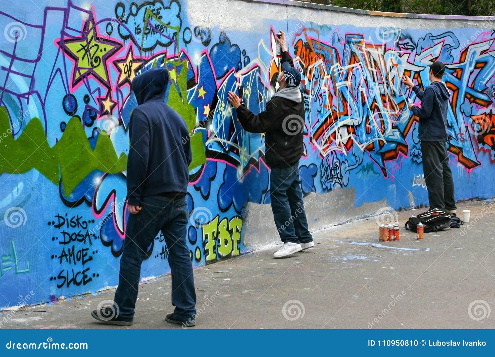 Drie jongens die graffiti schilderen
