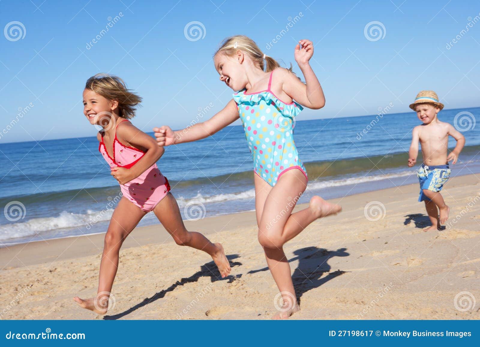Drie Kinderen die langs Strand lopen