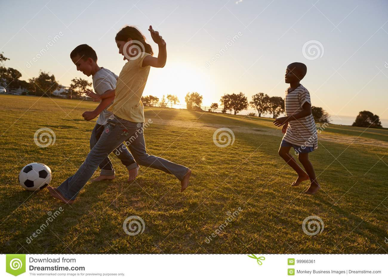 Drie kinderen die voetbal op een gebied spelen