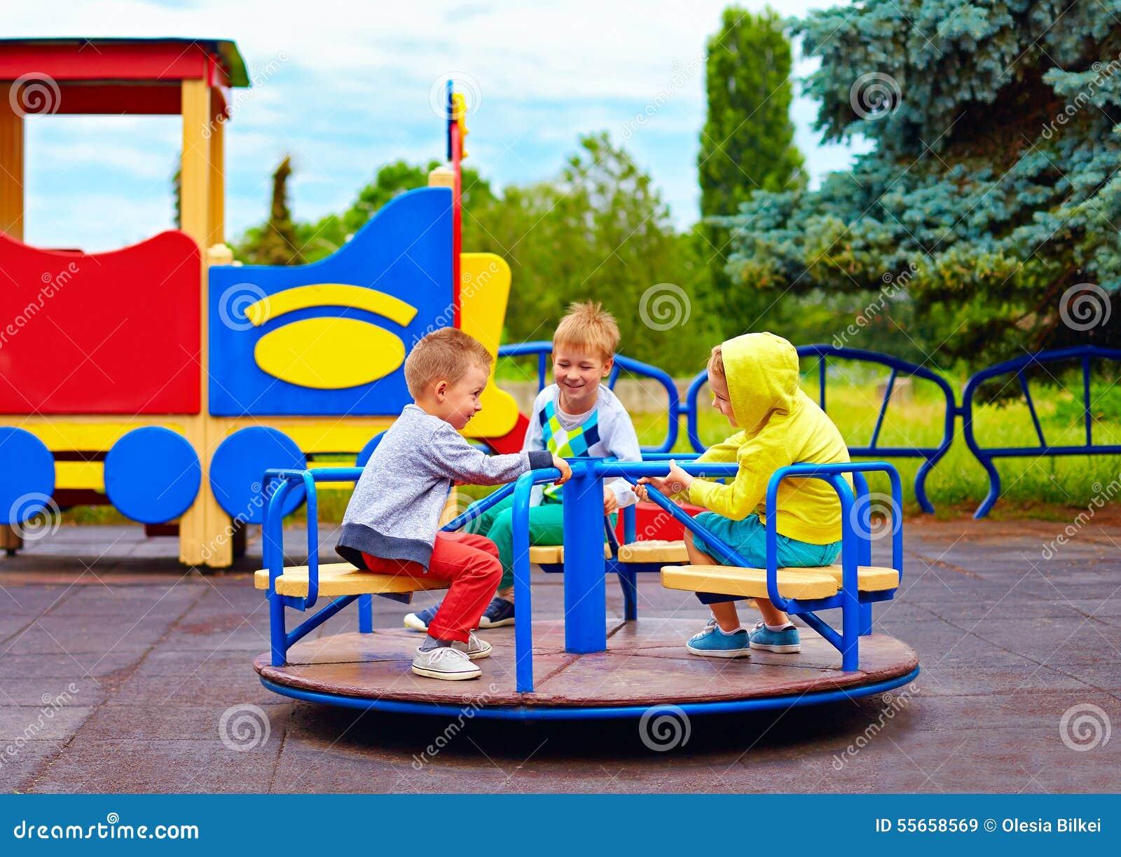 Drie kleine vrienden, jonge geitjes die pret op rotonde hebben bij speelplaats