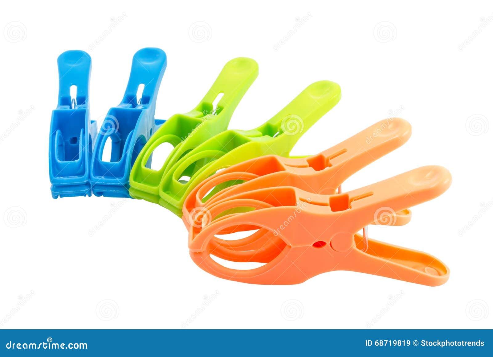 Drie klemmen van de kleuren plastic lente die over witte achtergrond worden geïsoleerd