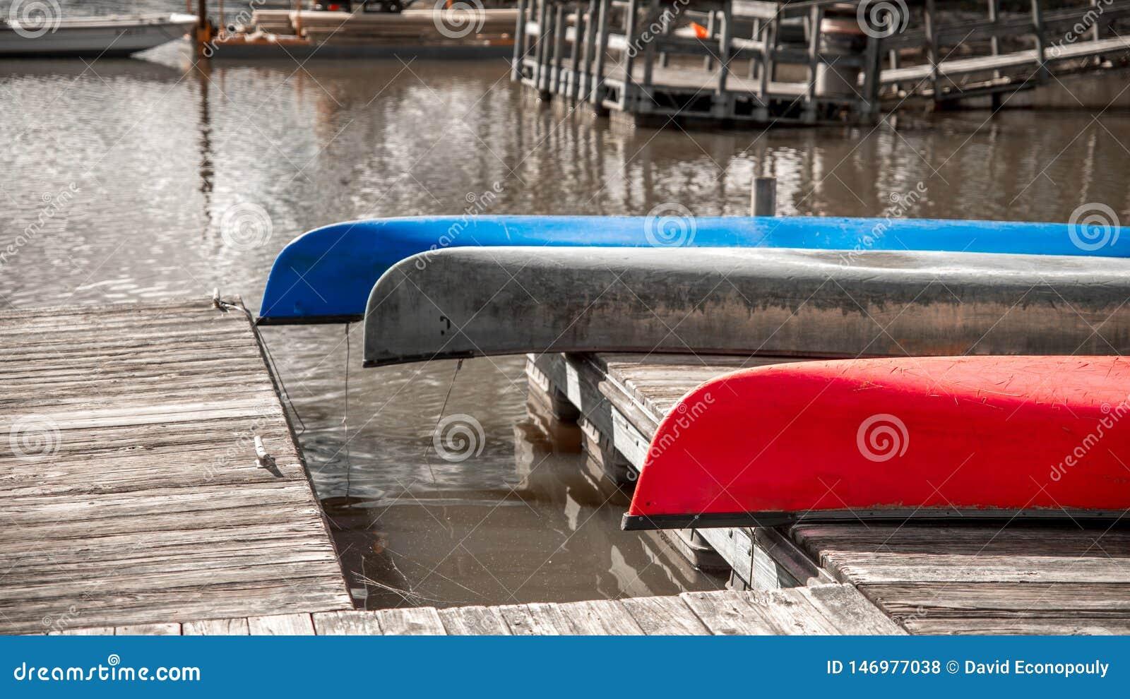 Drie kleurrijke kano s die bovenkant rusten - neer op een dok