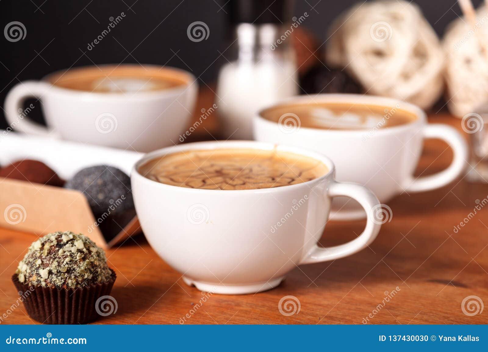Drie lattekoppen en kleine cakes op de houten lijst in de koffie Mededeling meer dan een Kop van koffie, koffiepauze
