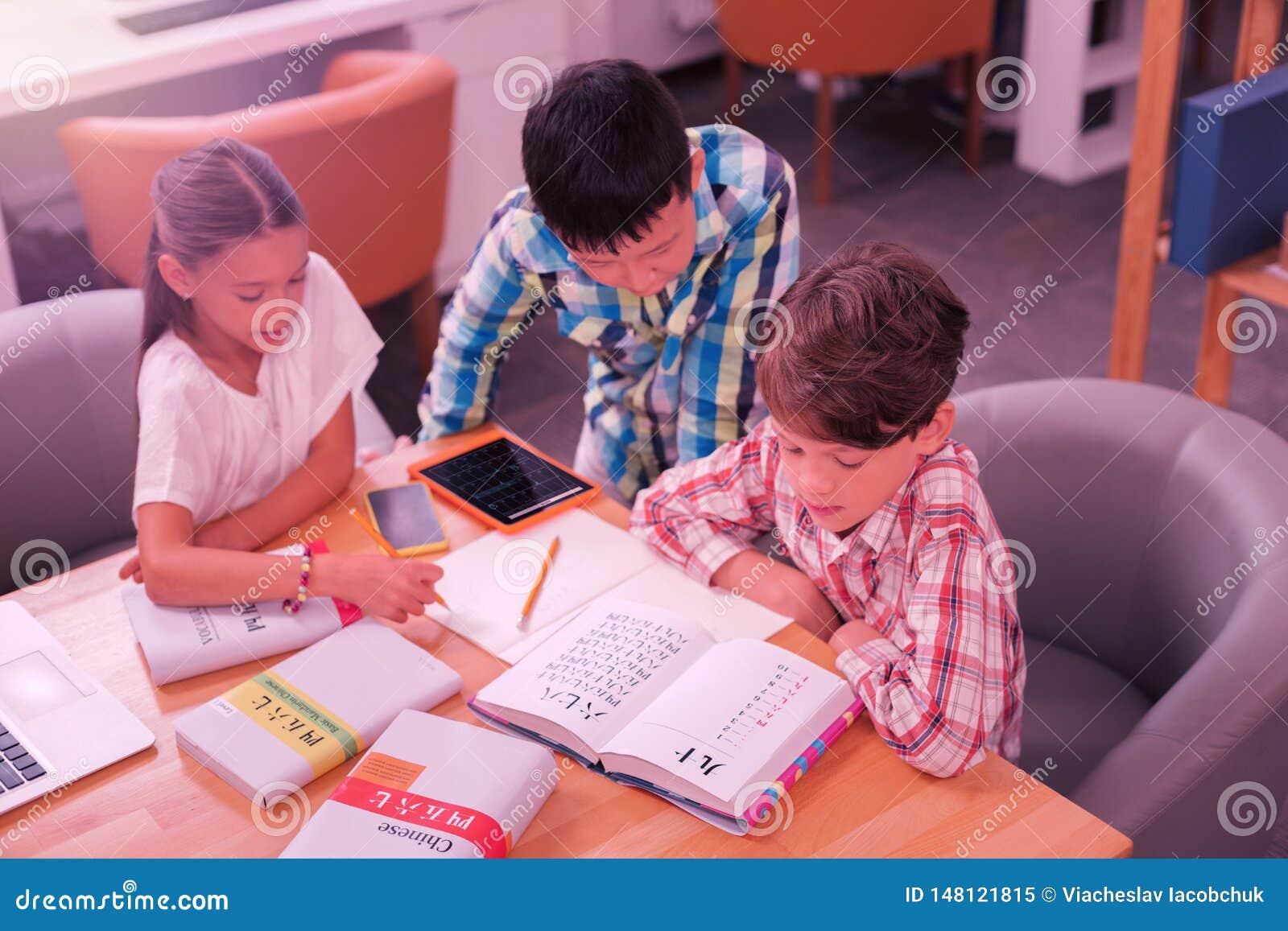 Drie leerlingen die over boeken in het klaslokaal poring