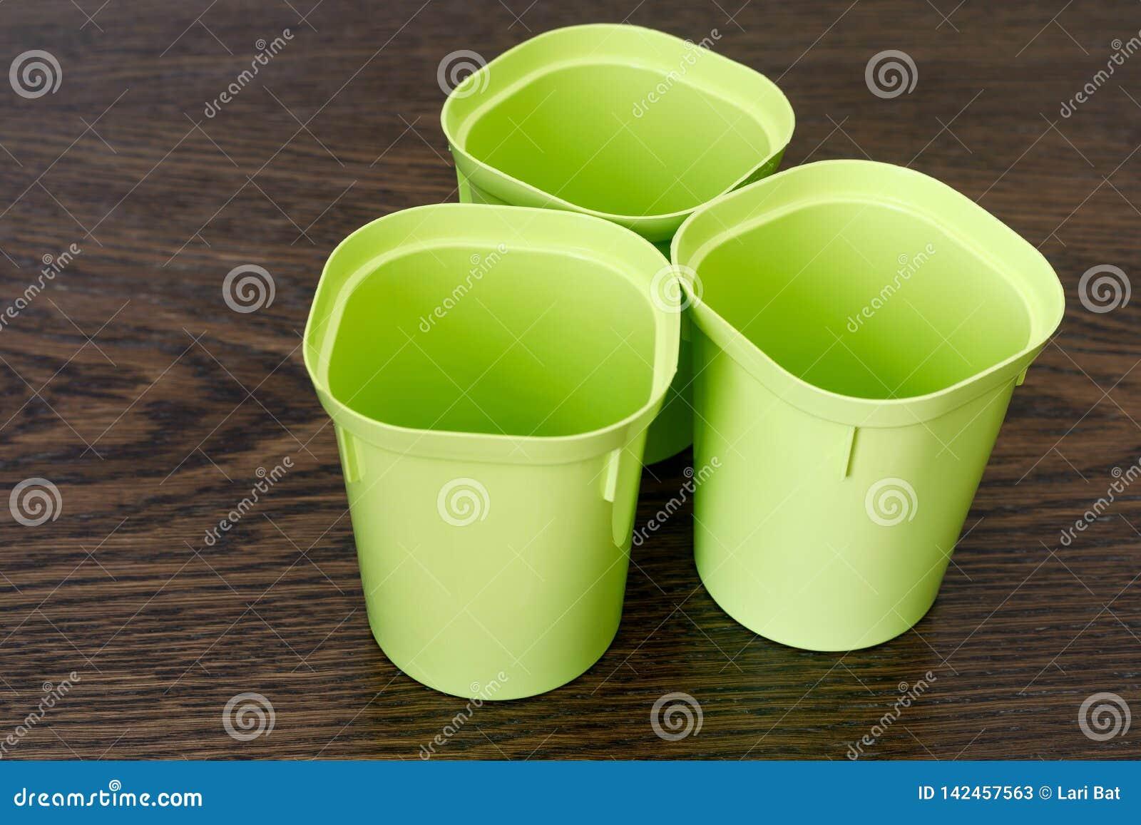 Drie lege plastic koppen voor zaailingen Bloementeeltpunten