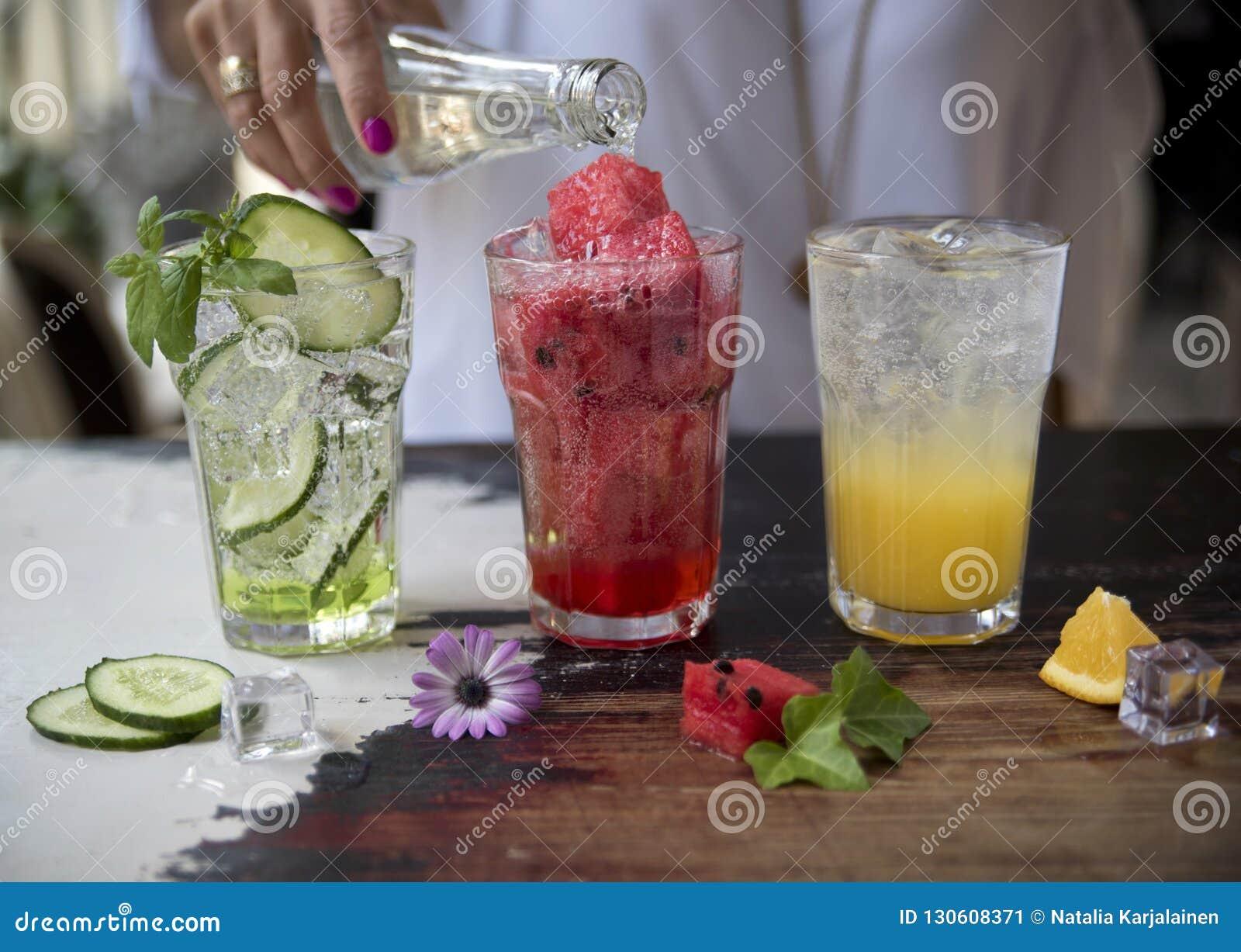 Drie limonades Komkommer, watermeloen en sinaasappel op rustieke achtergrond Op de achtergrond de hand van een meisjes gietend mi