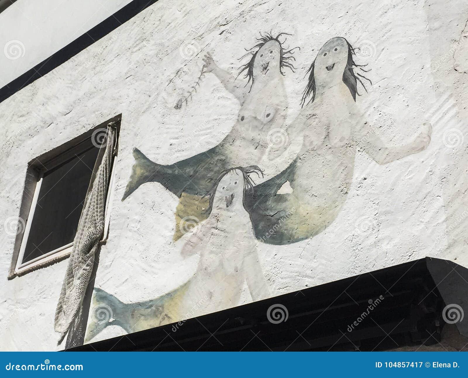 Drie meerminnen op een witte muur