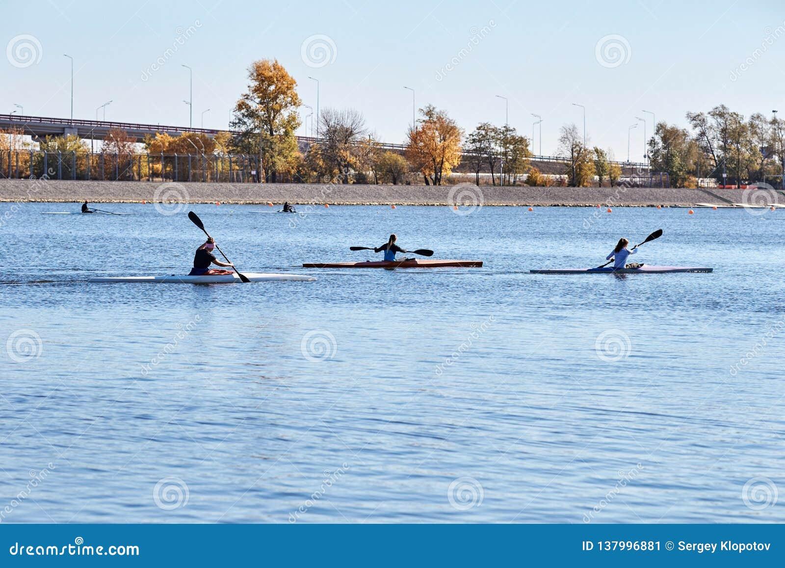 Drie meisjes zwemmen in sportenkajaks