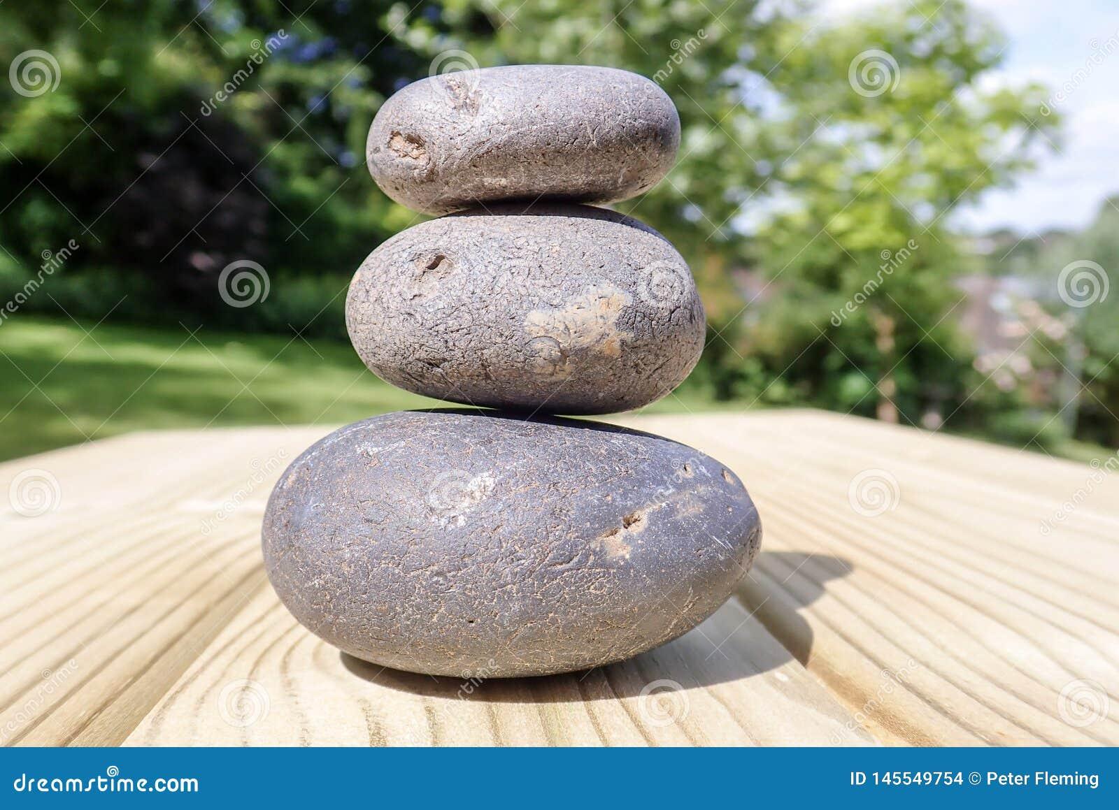 Drie opgestapelde stenen op de oppervlakte van het pijnboomhout