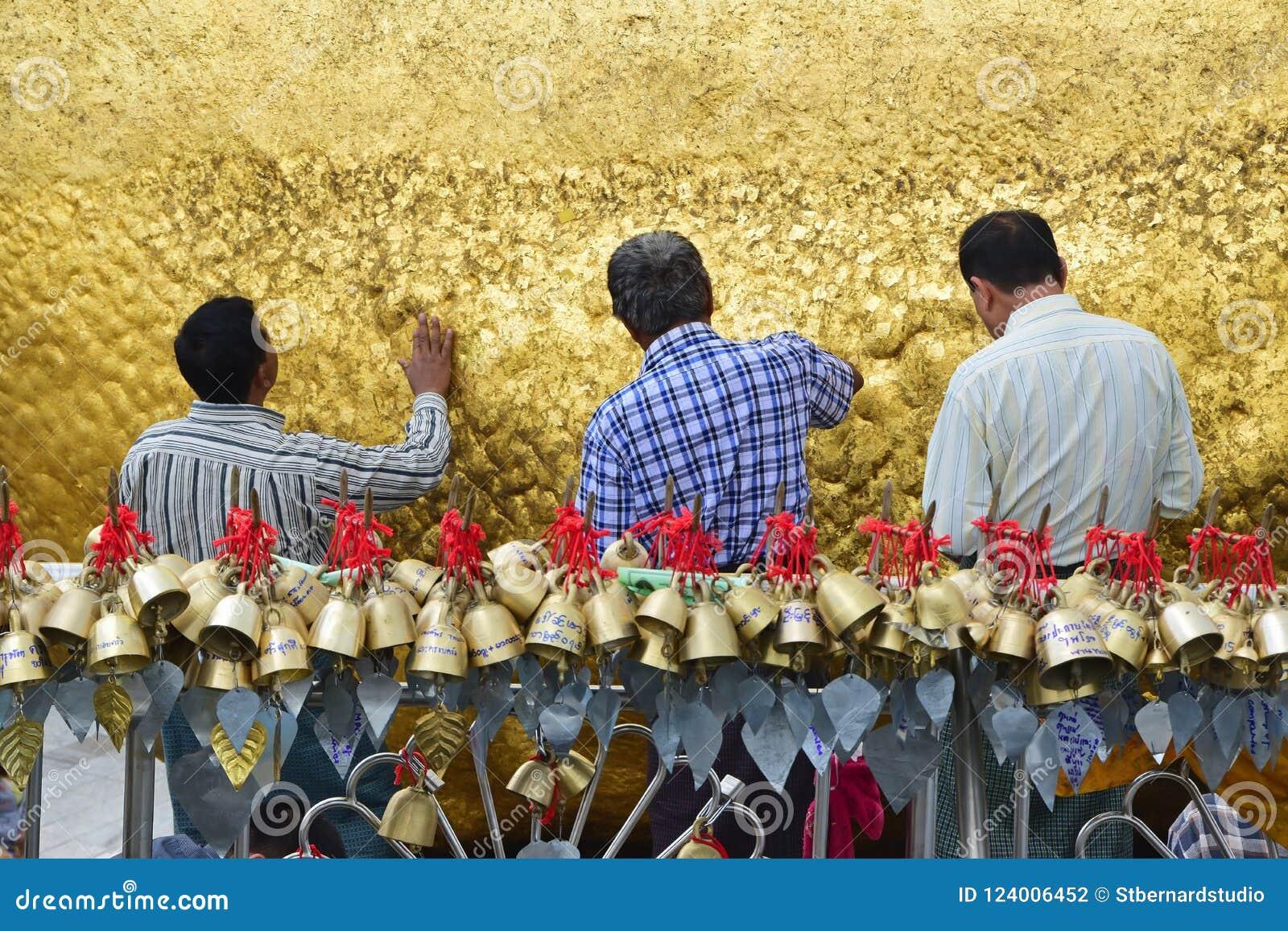 Drie Pelgrims die gouden foliesbladeren samen op gouden rots kleven bij de Kyaiktiyo-Pagode met kleine klokken in voorgrond