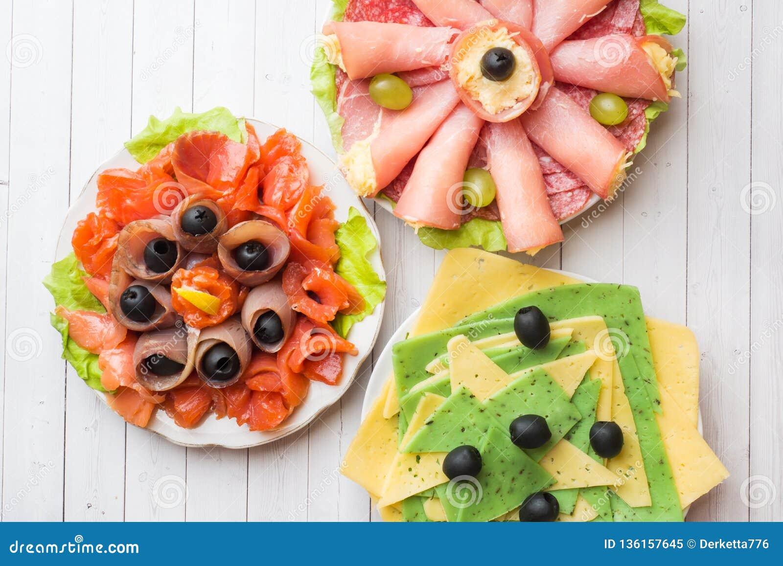 Drie platen van voorgerechten Hambroodje met kaas en rode vissen, snijdende verschillende types van kaas