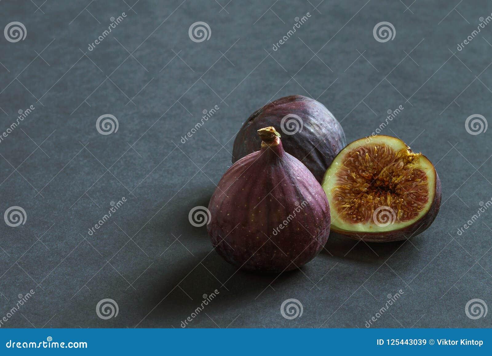 Drie rijpe fig.vruchten op een grijze achtergrond