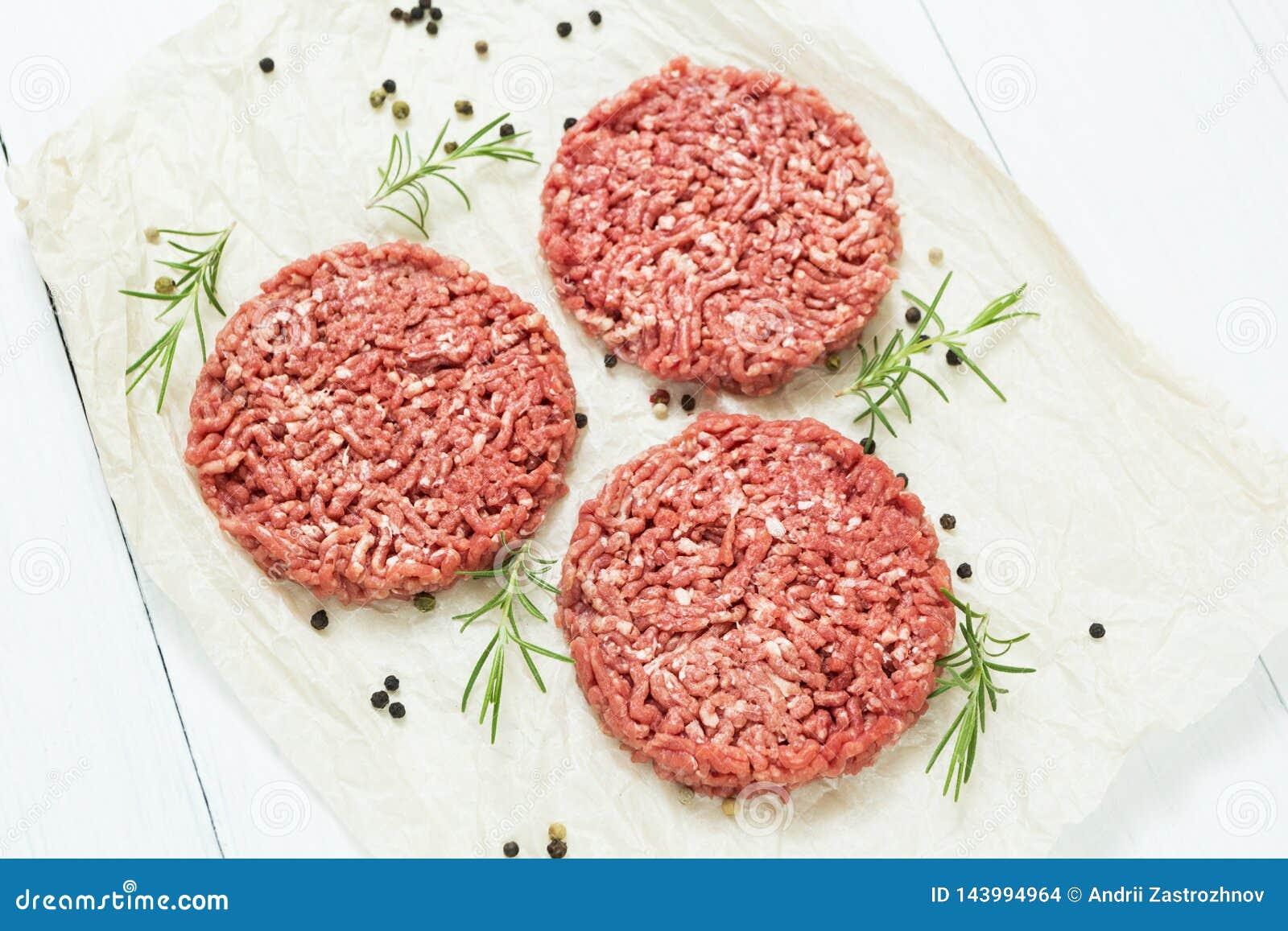 Drie ruwe hamburgers maakten van organisch vlees op een witte houten achtergrond met kruiden Hoogste mening