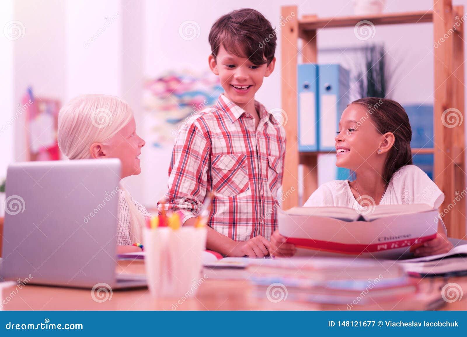 Drie schoolkinderen die bij elkaar glimlachen terwijl het leren van Chinees