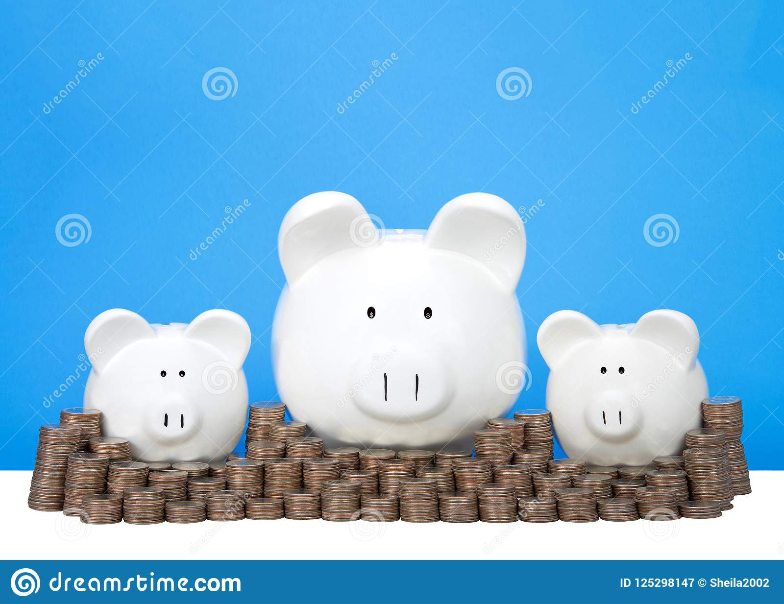 Drie spaarvarkens op een rij met stapels van muntstukken blauwe achtergrond