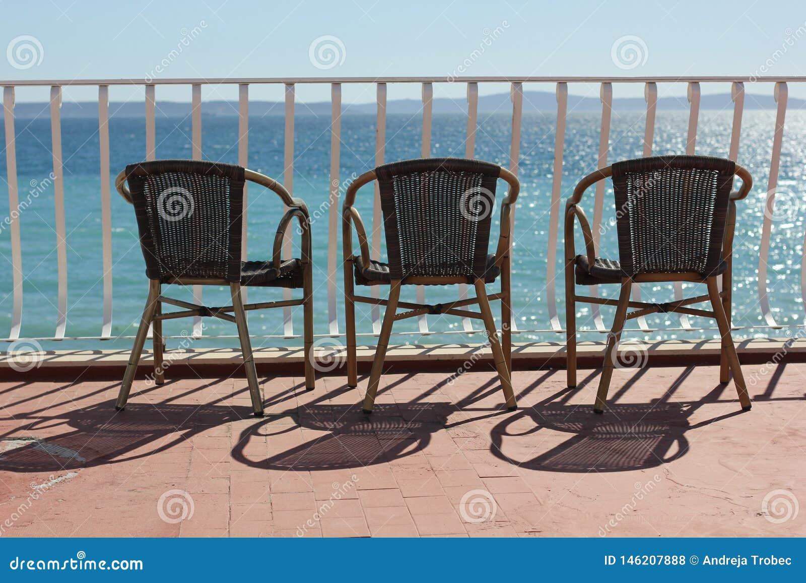Drie stoelen in terace boven kleurrijke Adriatische overzees