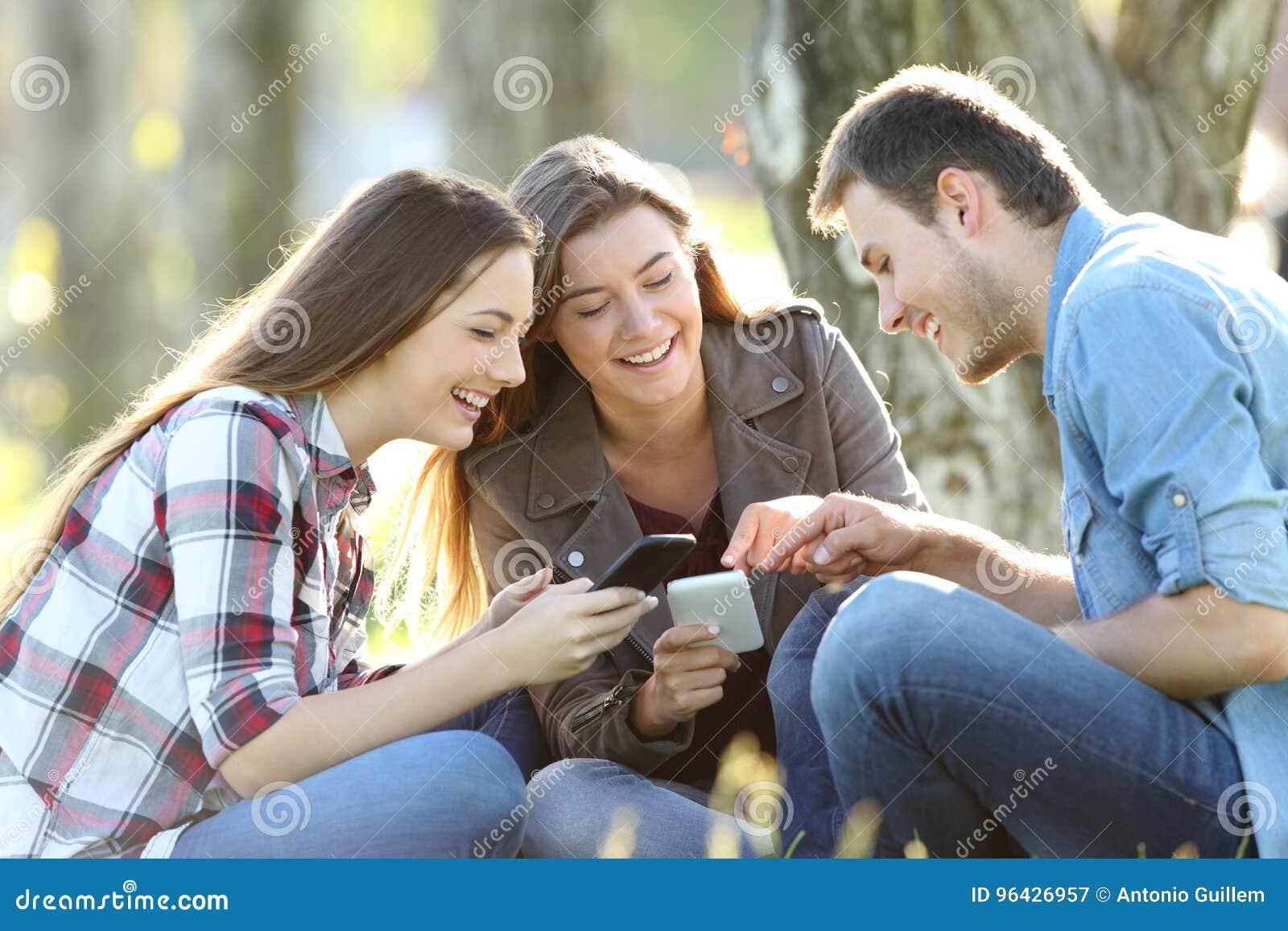 Drie tienerjaren die online inhoud op telefoons delen