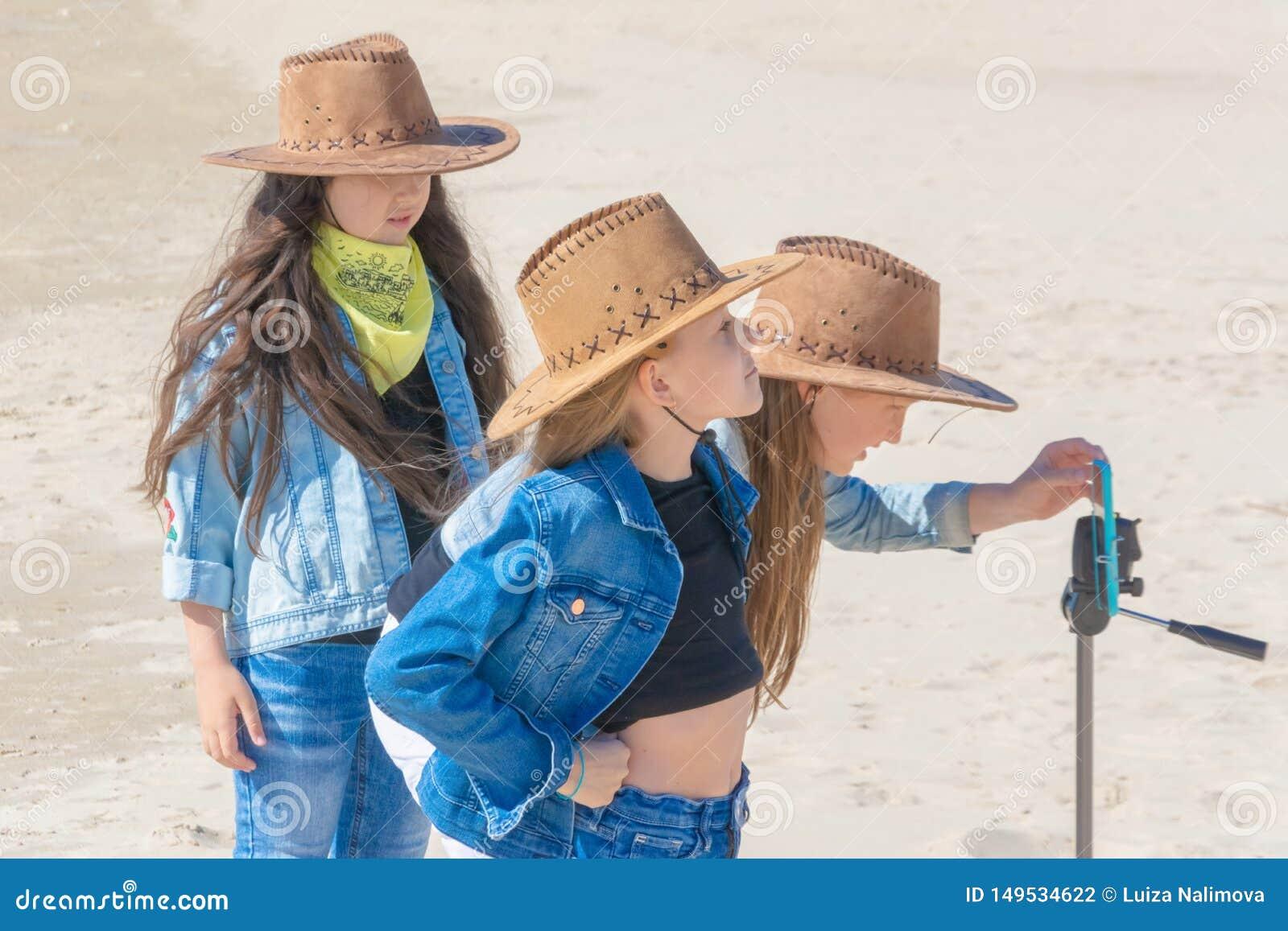 Drie tienermeisjes nemen een selfie op een telefoon op een zonnige dag