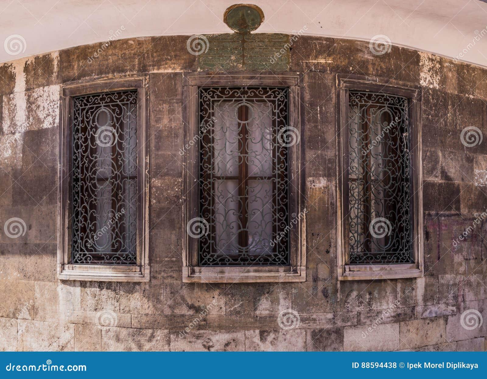 Drie vensters met gesierd metaalrooster op een steengebouw