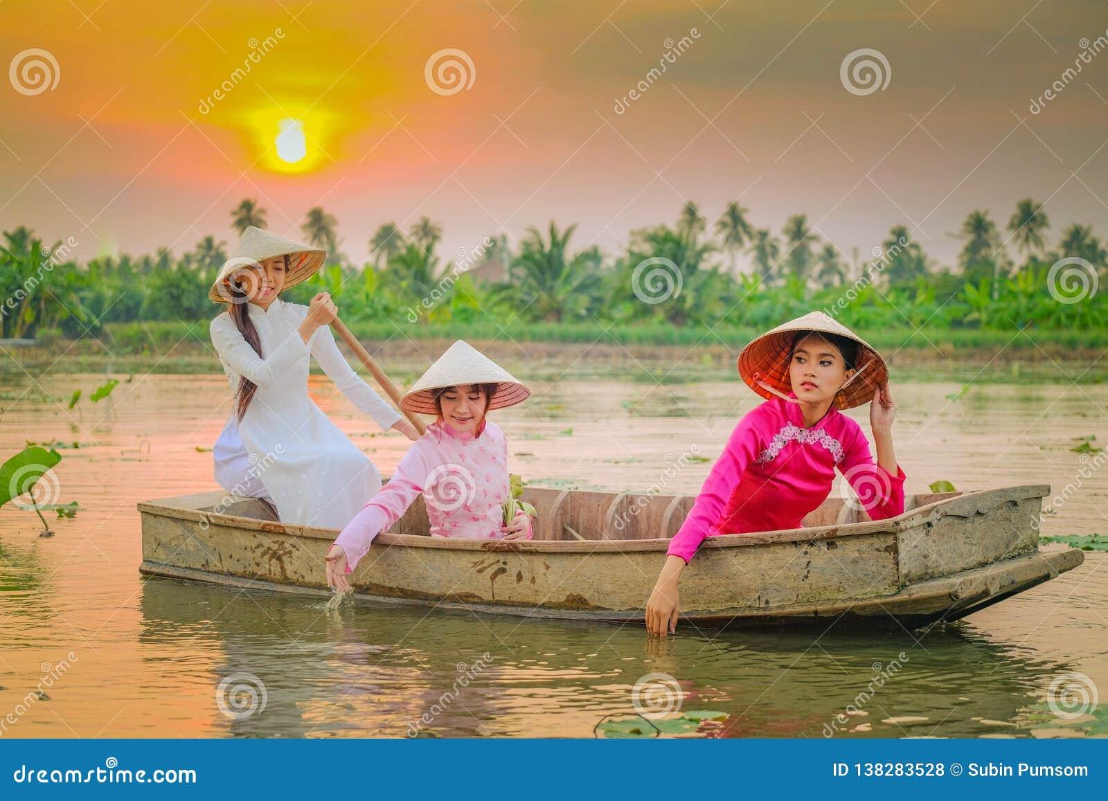 Drie Vietnamese meisjes roeien in de lotusbloemtuin