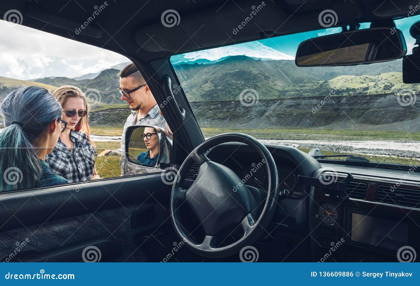 Drie vrienden dichtbij de auto bespreken de route in de reis Het concept van de reisvakantie