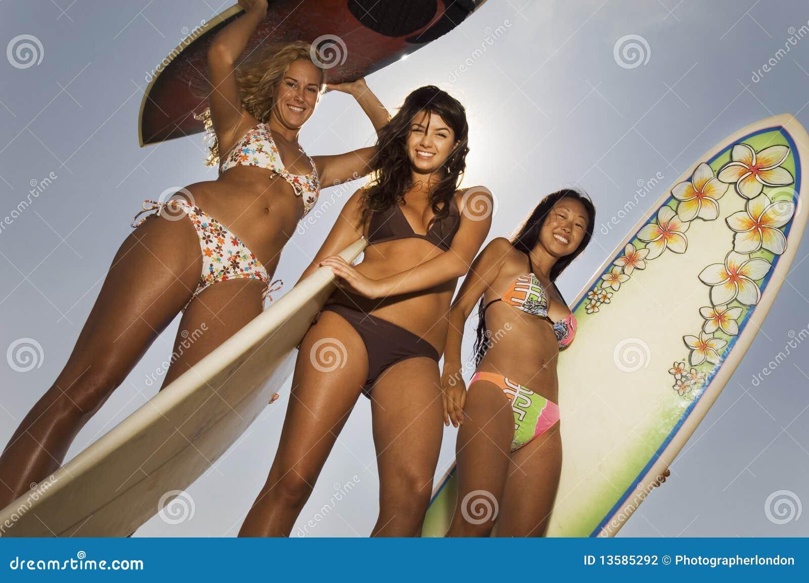 Drie vrouwelijke surfers die surfplanken in openlucht houden
