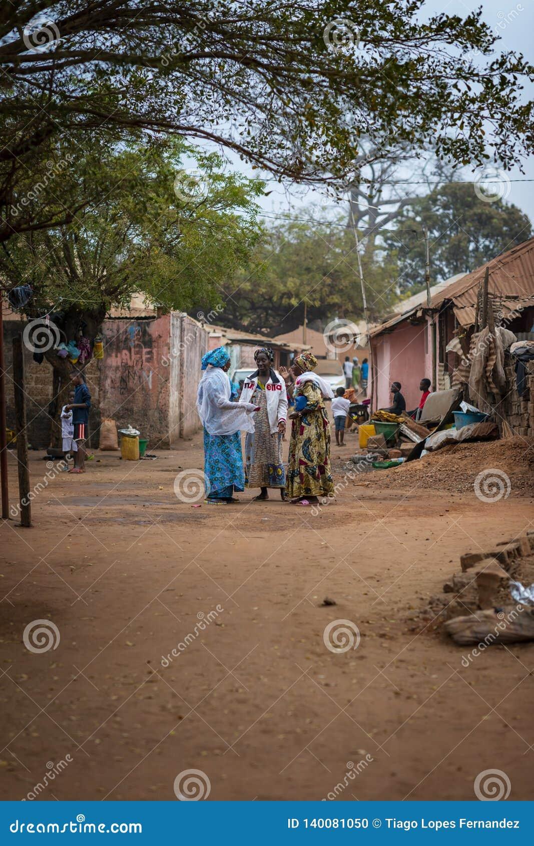 Drie vrouwen die op een straat bij de Missira-buurt, in de stad van Bissau spreken