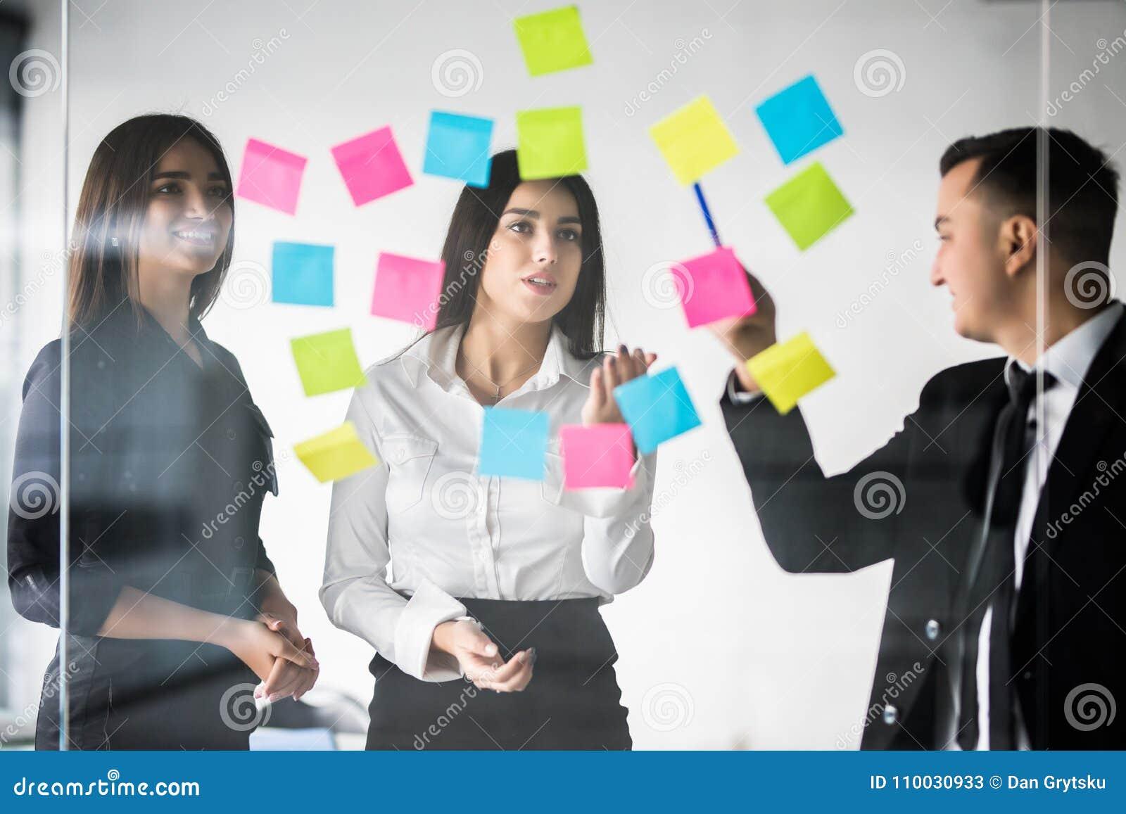 Drie zakenlui die en concept bespreken plannen Voorzijde van de teller en de stickers van de glasmuur Startbureau