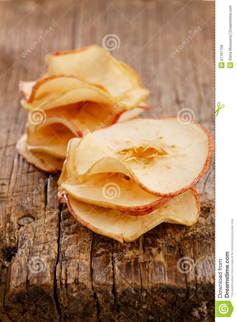 Dried apples slices on old wooden table stacked