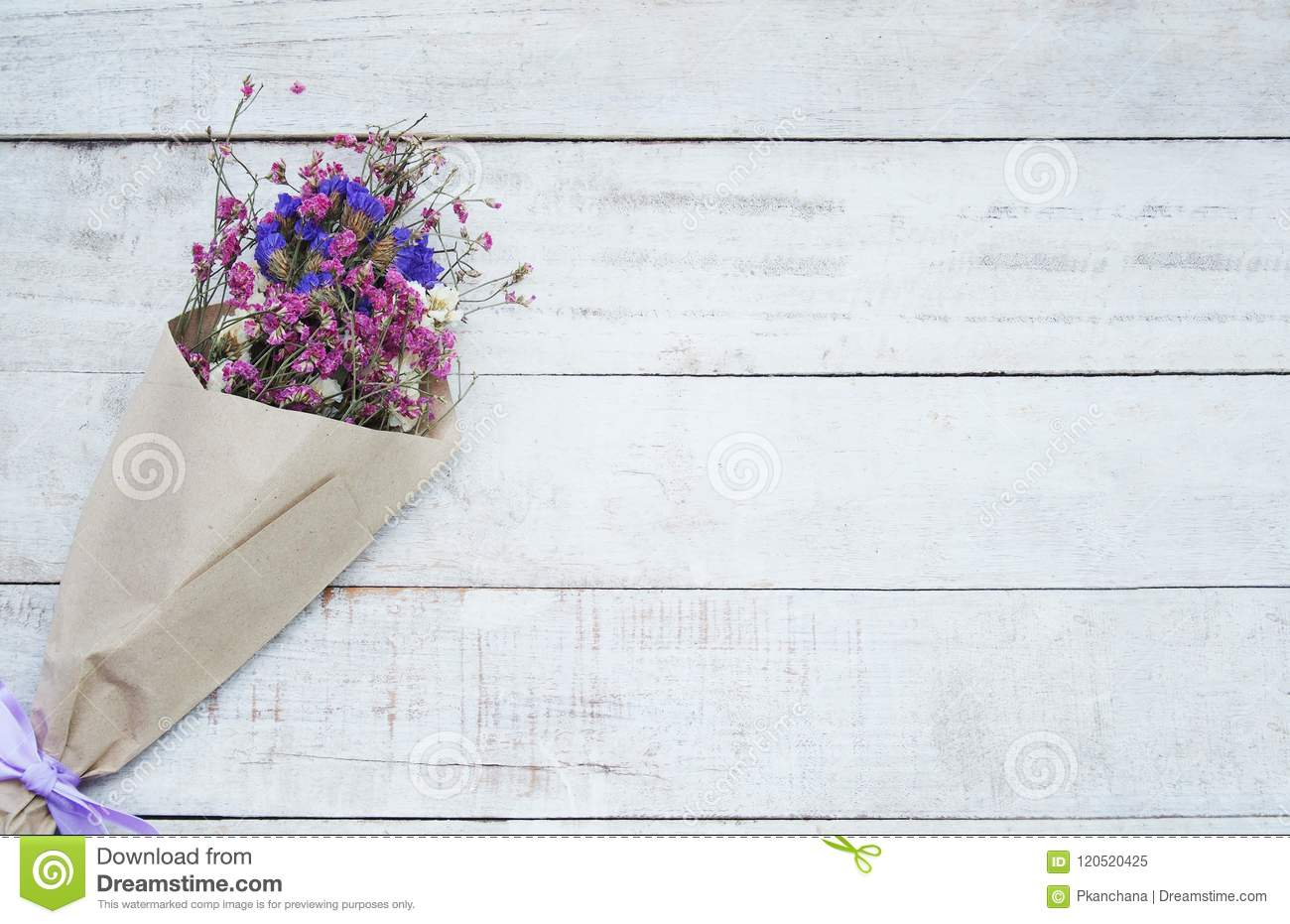 Dried Flower Bouquet In Brown Paper On Wood Background Stock Image
