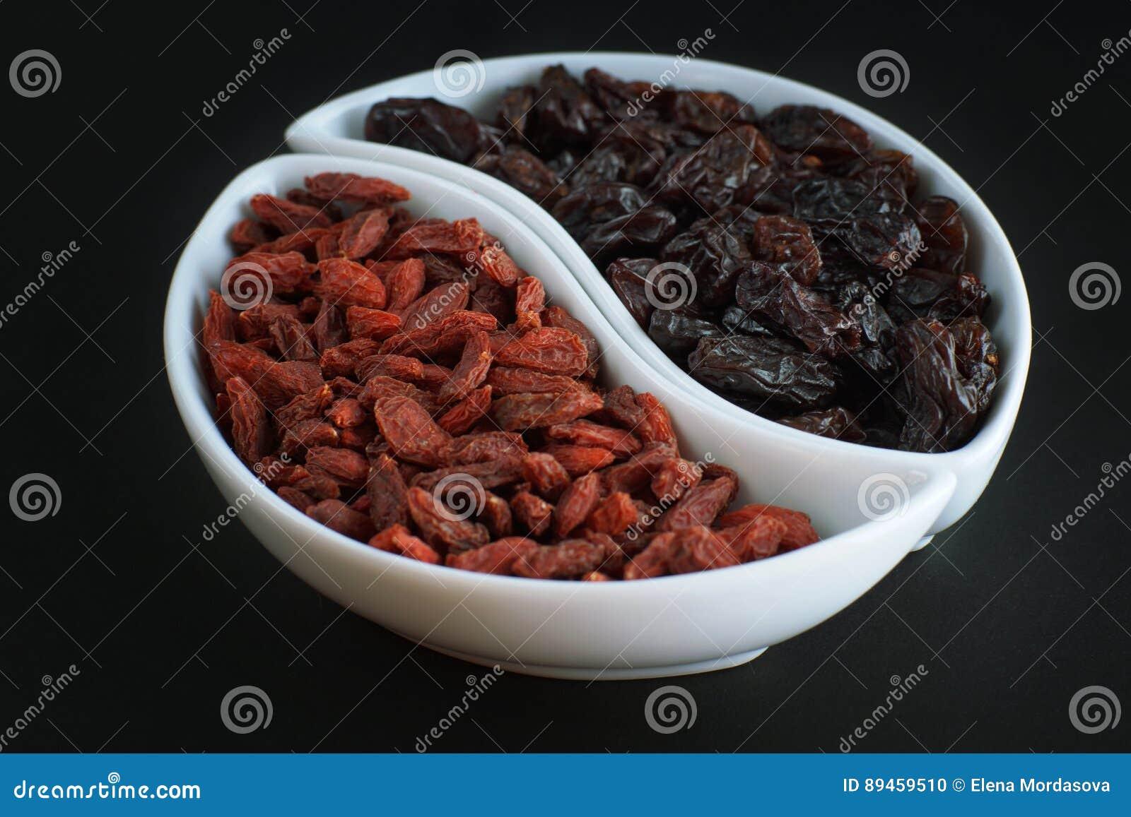 dried goji berries and raisins in bowls on a dark background