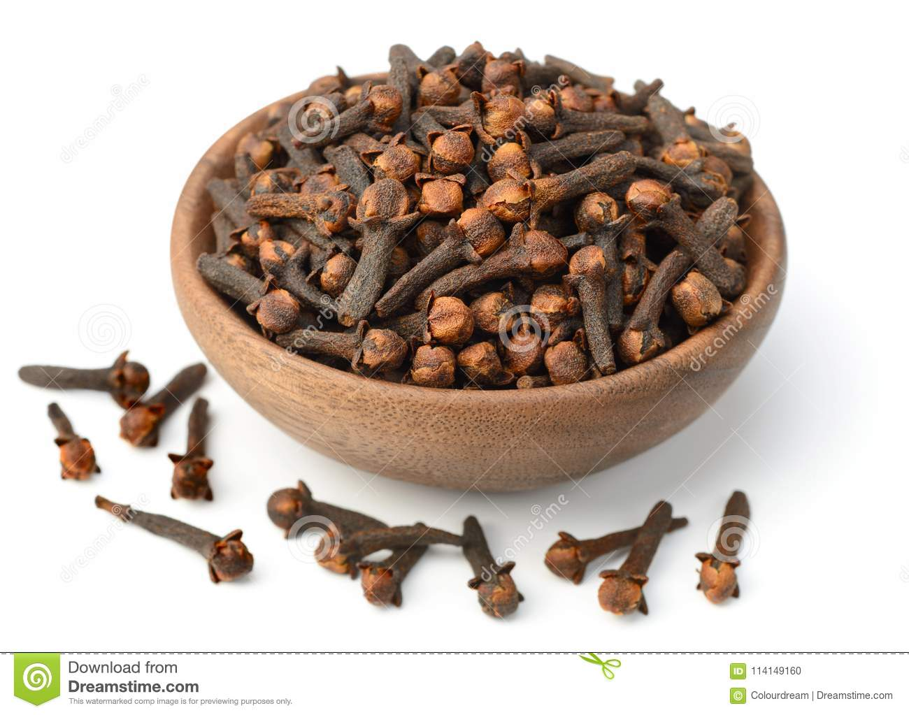 Dried herb, dried cloves in the wooden plate, on white