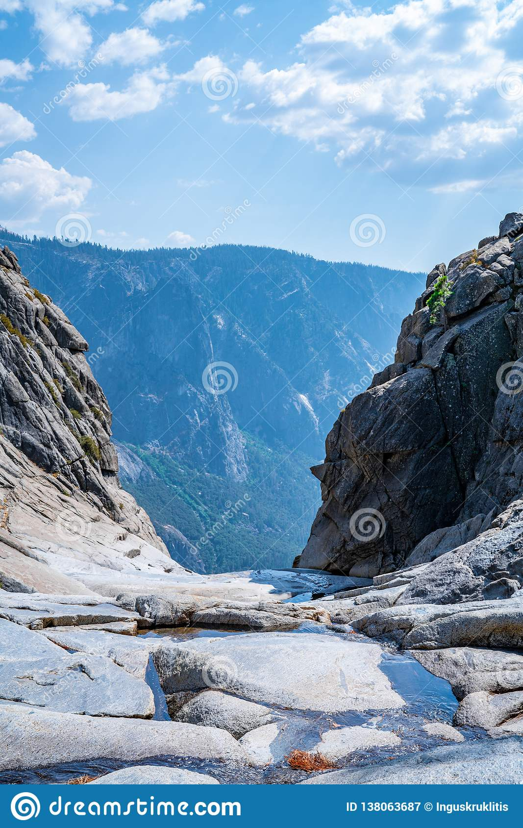 Dried out Yosemite waterfall with small river and pond where used to be mighty falls.