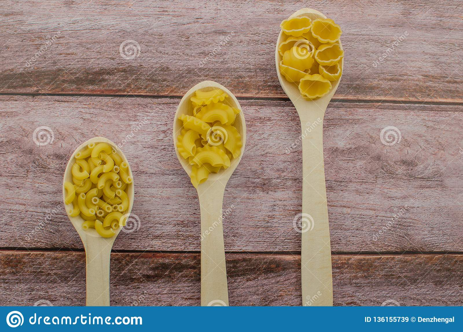Dried Pasta Food Selection In Wooden Spoons Over Old Oak