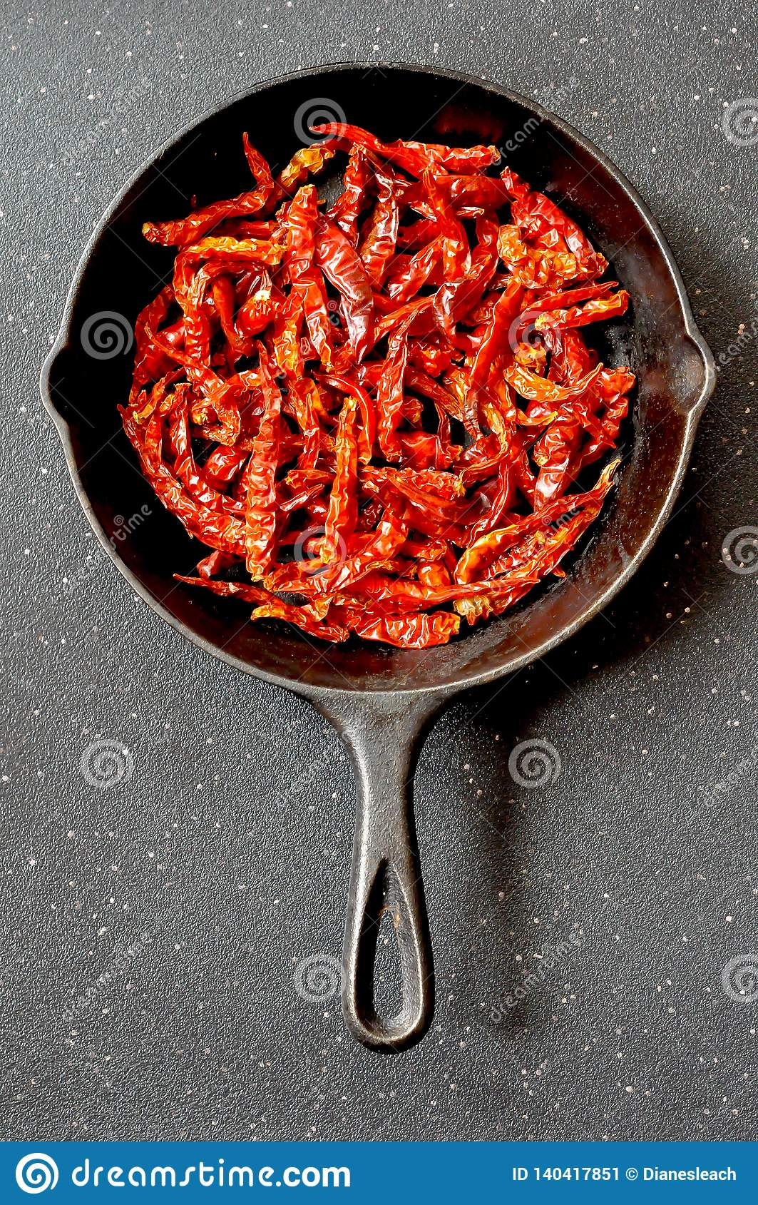 Dried red chili peppers in a cast iron frying pan, top view