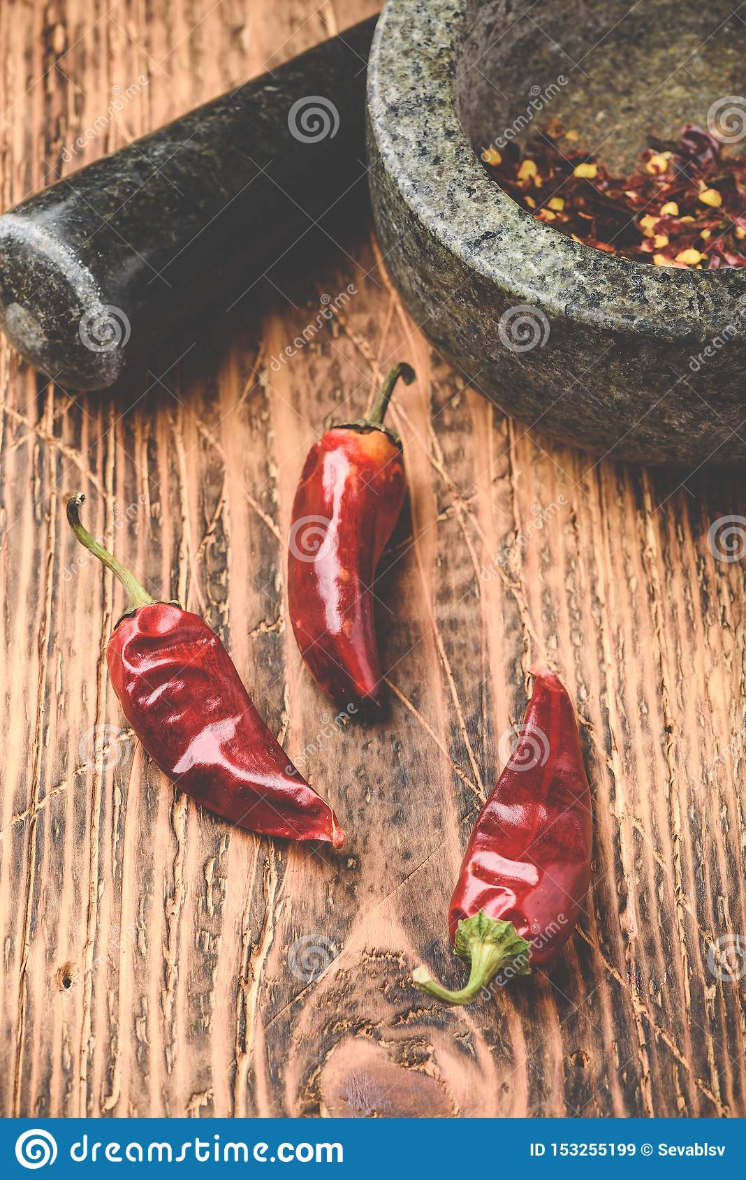 Dried red chili peppers on wooden surface with mortar and pestle
