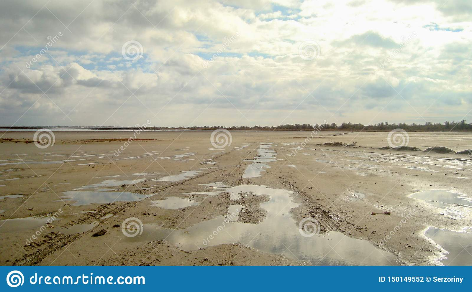 Dried up sandy estuary under the boundless cloudy sky