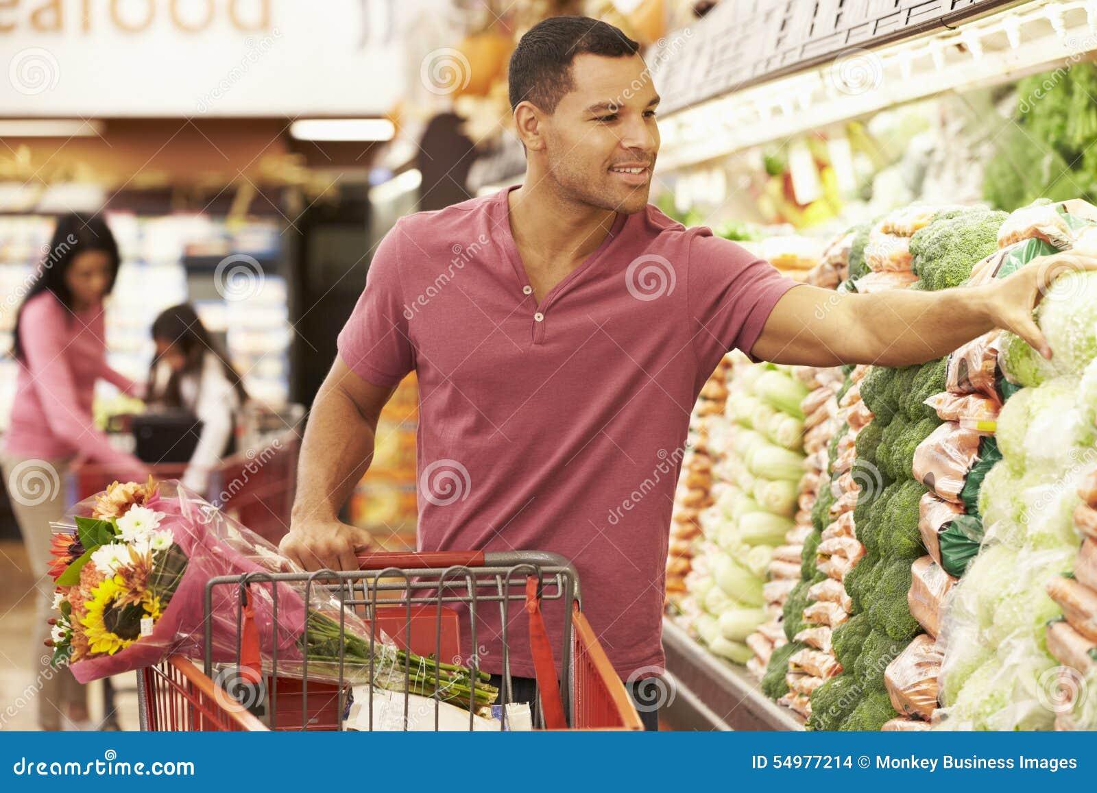 Driftig spårvagn för man vid jordbruksprodukterräknaren i supermarket