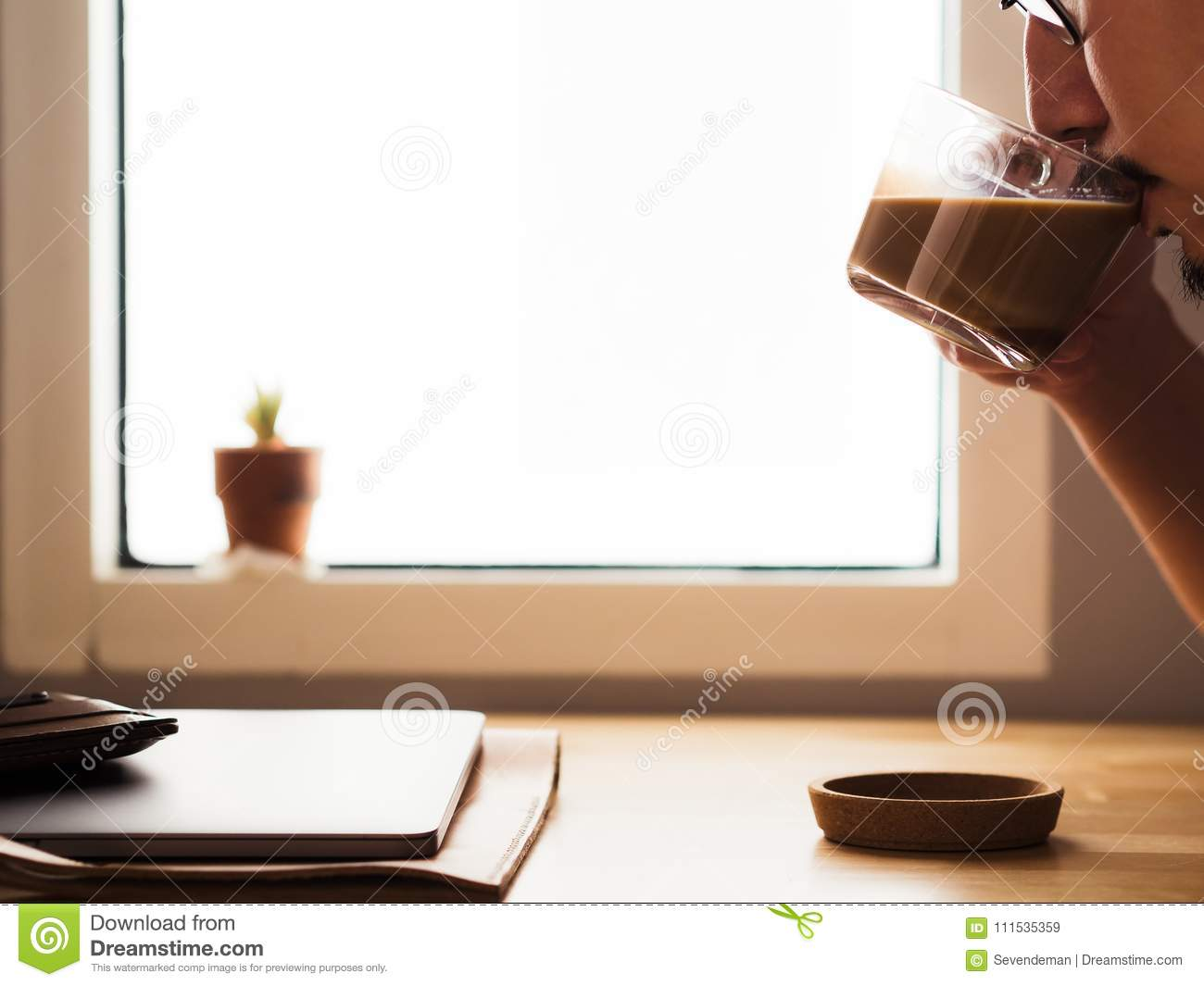 Drinking coffee on workspace desk with laptop by the window light.