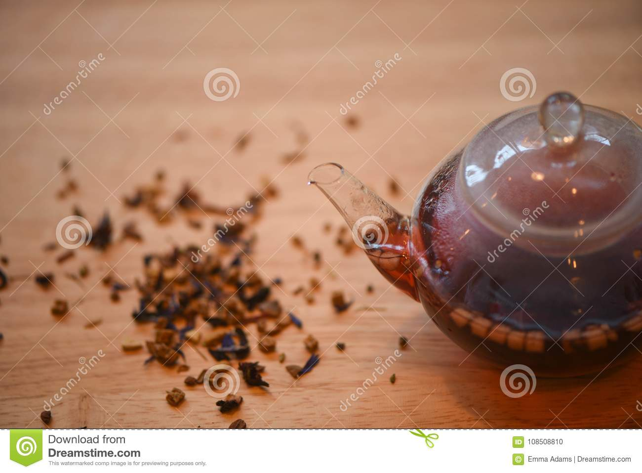 Drink photography of a close up glass teapot filled with hot red color apple spice fruit flavor tea with scattered leaves on wood