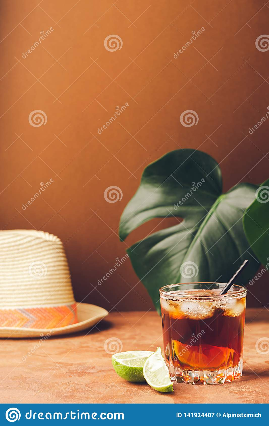 A drink of rum or cola ice cubes and juicy lime in glass goblets against a background of tropical green leaves.