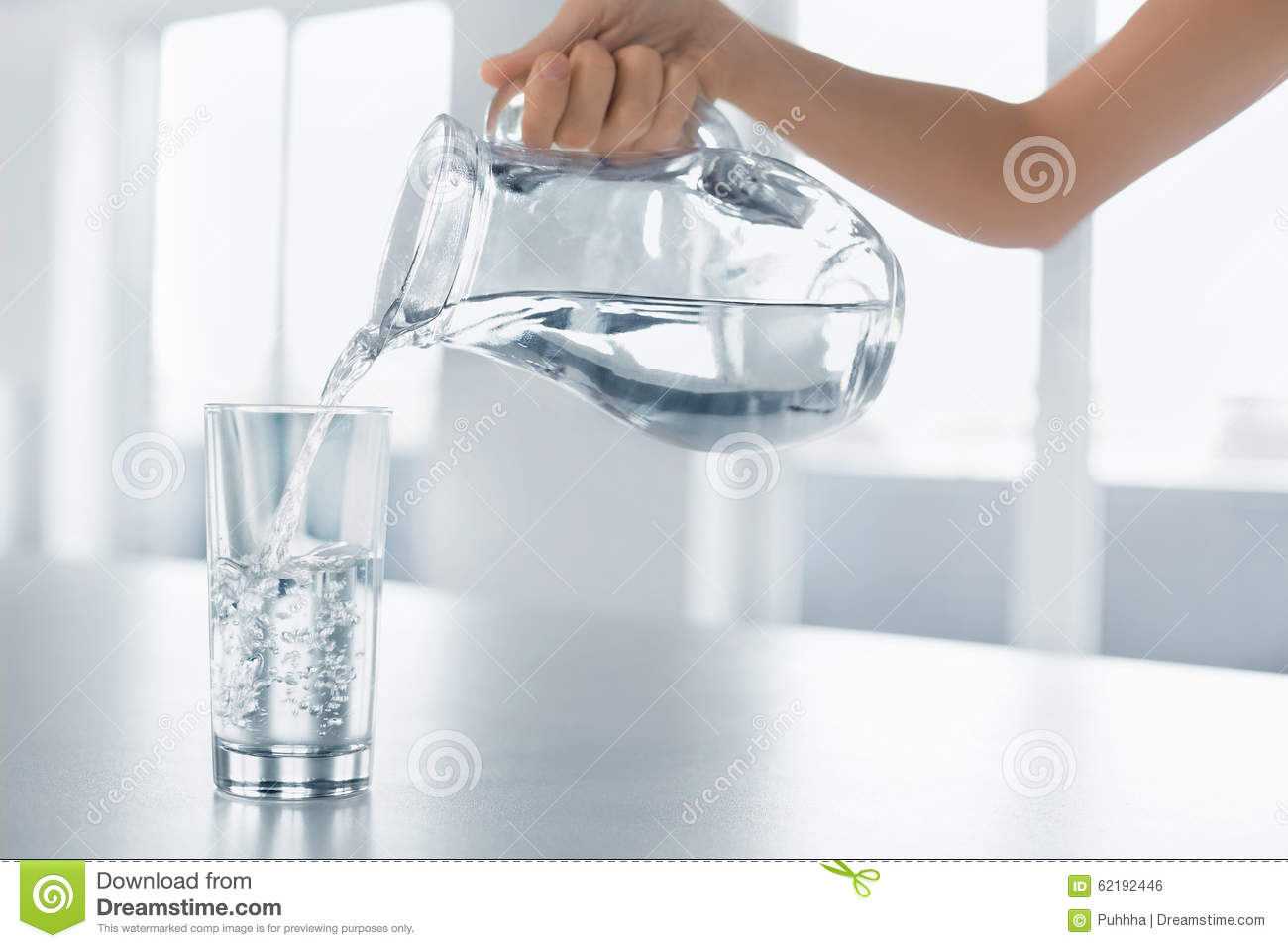 Drink Water. Woman s Hand Pouring Water From Pitcher Into A Glas
