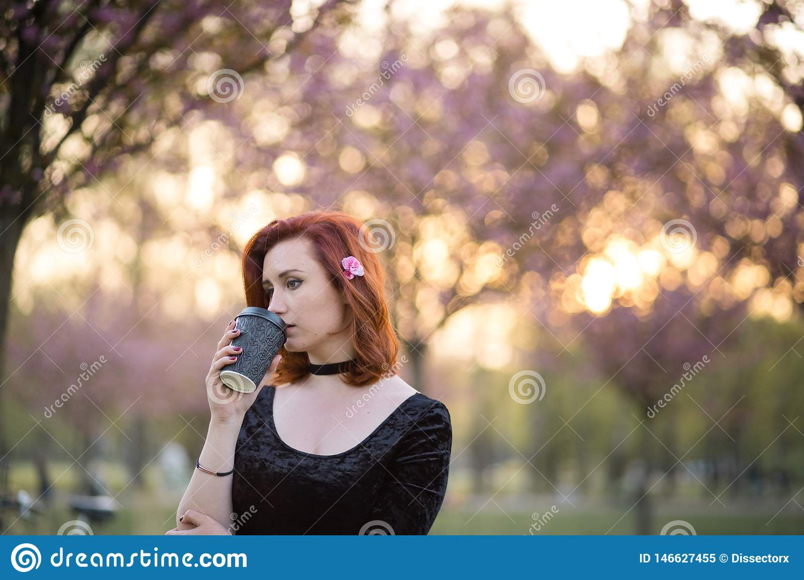 Drinking coffee from paper mug cup - Happy young travel dancer woman enjoying free time in a sakura cherry blossom park