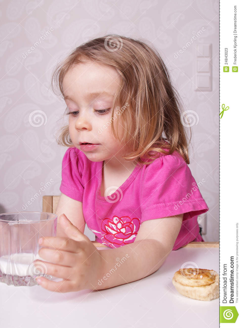 Young cute girl drinking a glass of milk and eating a cinnamon roll.