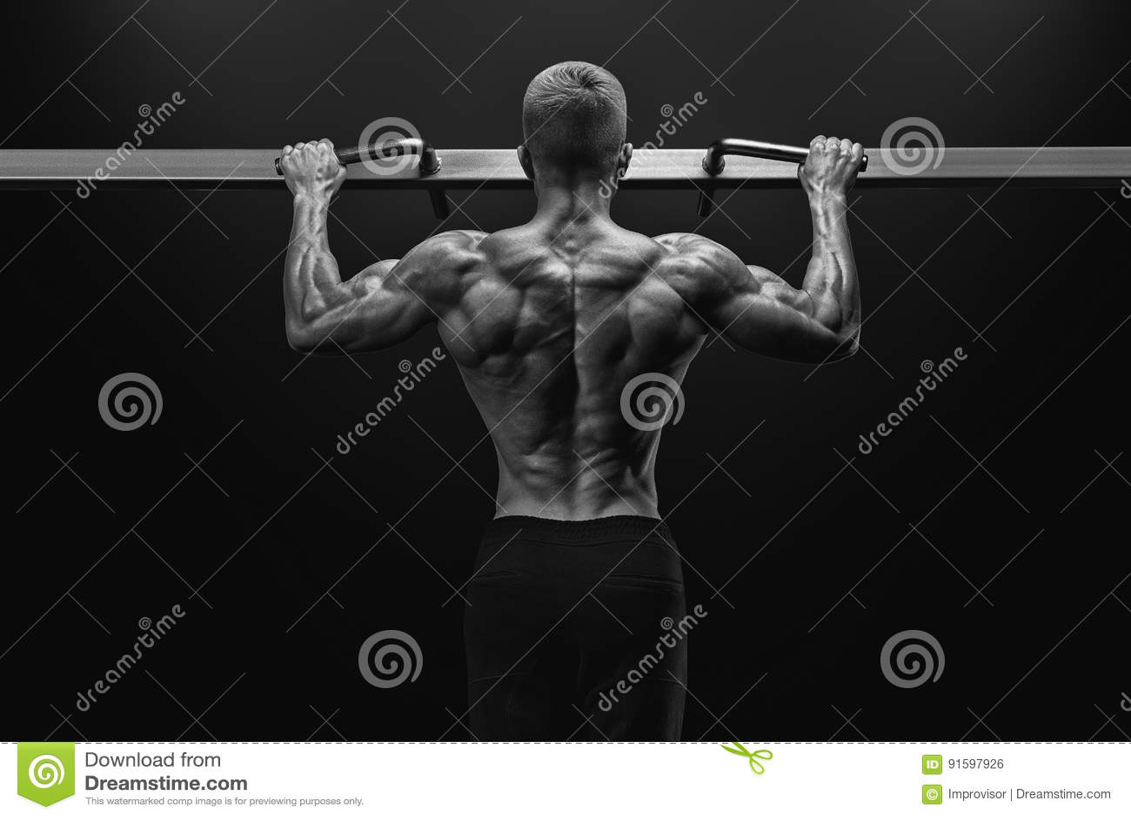 Driva den muskulösa kroppsbyggaregrabben som gör pullups i idrottshall Isolerat på vit bakgrund