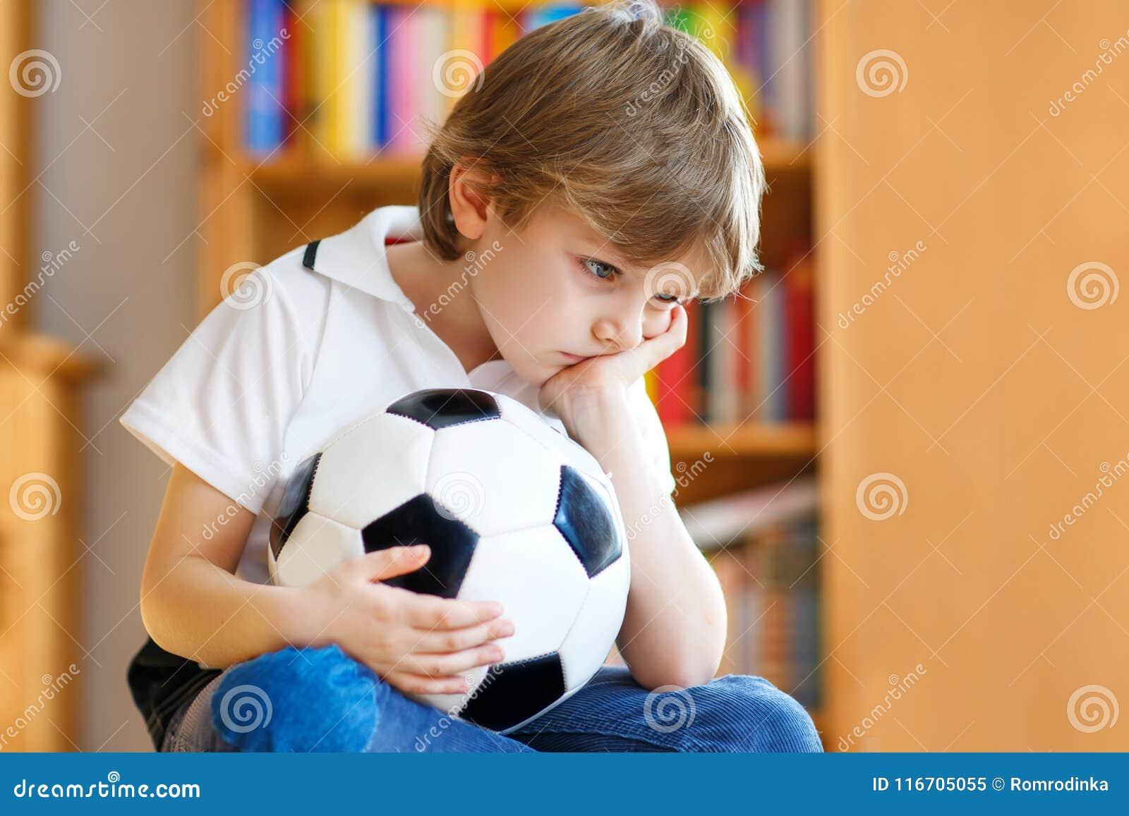 Droevig en niet gelukkig weinig jong geitje met voetbal over verloren voetbal of voetbalspel kind na het letten van op gelijke op
