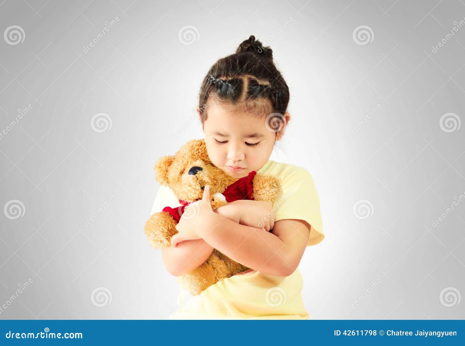 Droevig meisje die alleen teddybeer koesteren