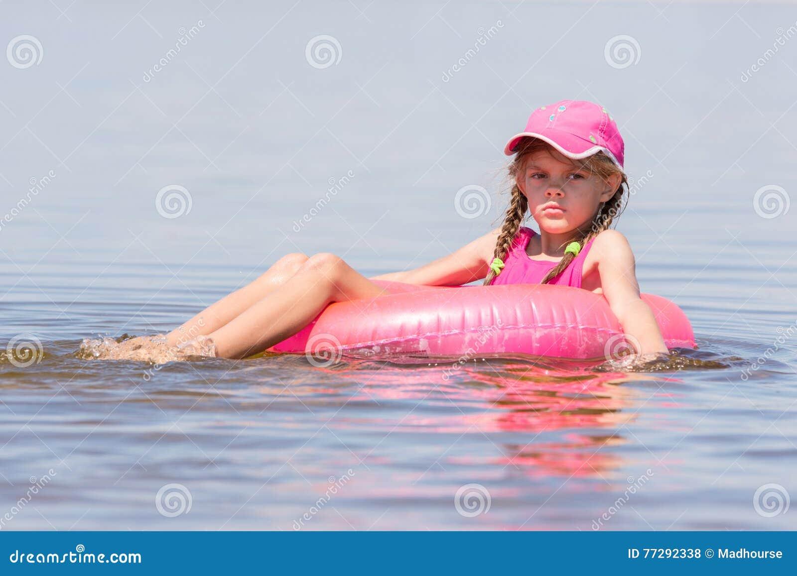 Droevig meisje in een GLB die die in rivier drijven op de zwemmende cirkel wordt gezeten